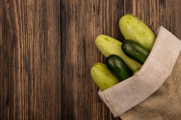 Vista dall'alto di verdure fresche come cetrioli e zucchine su un sacchetto di tela da imballaggio su una superficie in legno con spazio di copia