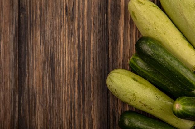 Vista dall'alto di verdure fresche come cetrioli e zucchine isolate su una parete in legno con spazio di copia