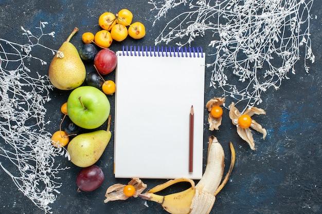 Vista dall'alto di verdure fresche come pere mele verdi ciliegie gialle prugne e blocco note sulla scrivania blu, frutta fresca frutti di bosco cibo