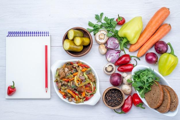 Vista dall'alto di verdure fresche come cipolle carote pepe con pagnotte di pane e piatto di carne a fette su vitamina pasto leggero e vegetale