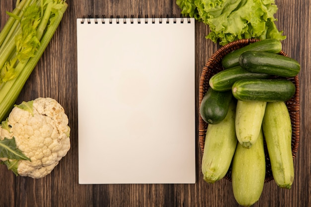 Top view of fresh vegetables such as zucchinis and cucumbers on a bucket with lettuce cauliflower and celery isolated on a wooden wall with copy space
