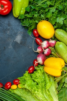 Vista dall'alto di verdure fresche pomodoro zucchine ravanello limone prezzemolo pomodorini lattuga su superficie scura con spazio libero