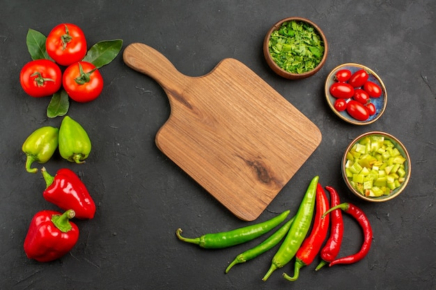 Вид сверху свежие овощи, помидоры и болгарский перец на темном столе, цвет спелой еды в салате