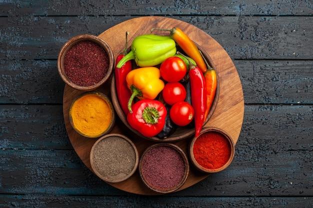 어두운 책상에 조미료와 상위 뷰 신선한 야채 토마토와 후추