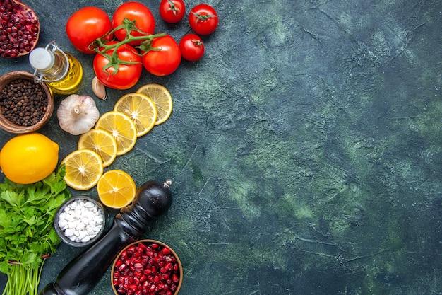 Вид сверху свежие овощи, помидоры, ломтики лимона, морская соль в маленькой миске, мельница для перца на кухонном столе со свободным пространством