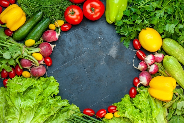Top view fresh vegetables tomatoes lettuce radish lemon zucchini parsley cherry tomatoes on dark surface free space in center