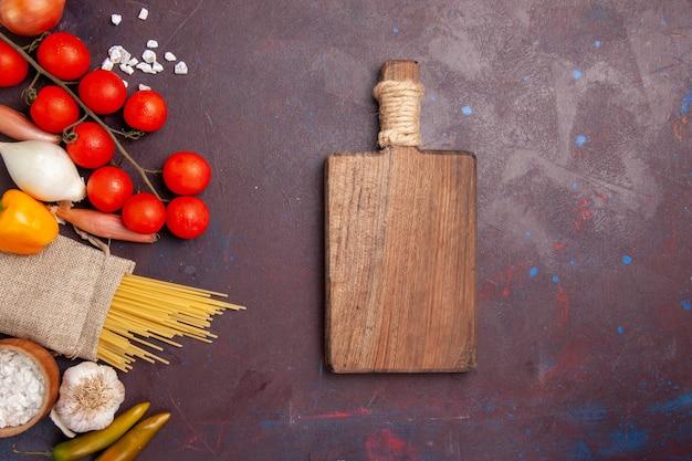 トップビュー新鮮な野菜トマト玉ねぎパスタと暗い机の上のジャガイモ