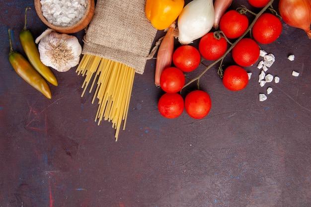 Vista dall'alto verdure fresche pomodori cipolle pasta e patate su uno spazio buio