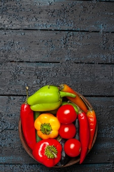 Top view fresh vegetables tomatoes and pepper on dark desk