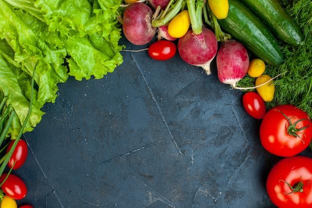 Vista dall'alto verdure fresche pomodori ravanello cetriolo aneto pomodorini lattuga su superficie scura con copia posto