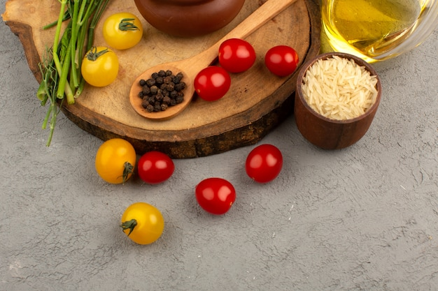 Vista dall'alto verdure fresche intere come pomodori gialli e rossi insieme con olio d'oliva sul grigio