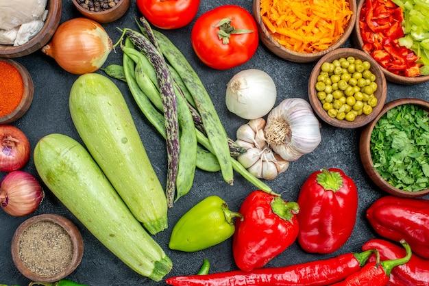 Vista dall'alto di verdure fresche con fagioli e condimenti sul pasto di insalata di tavola scuro maturo
