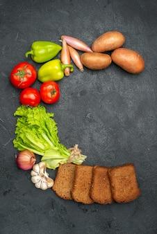 Vista dall'alto di verdure fresche con pagnotte di pane nero su insalata di pane grigio maturo