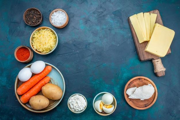 Вид сверху свежие овощи с сыром и приправами на синем фоне.