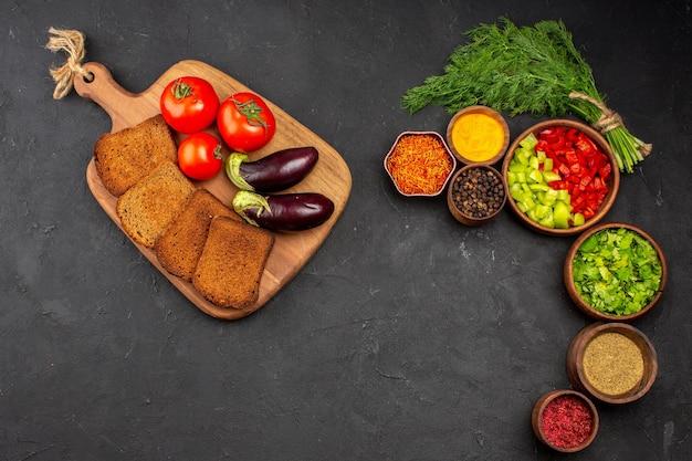 Vista dall'alto verdure fresche con pagnotte di pane scuro e condimenti sulla superficie scura insalata di pane cibo