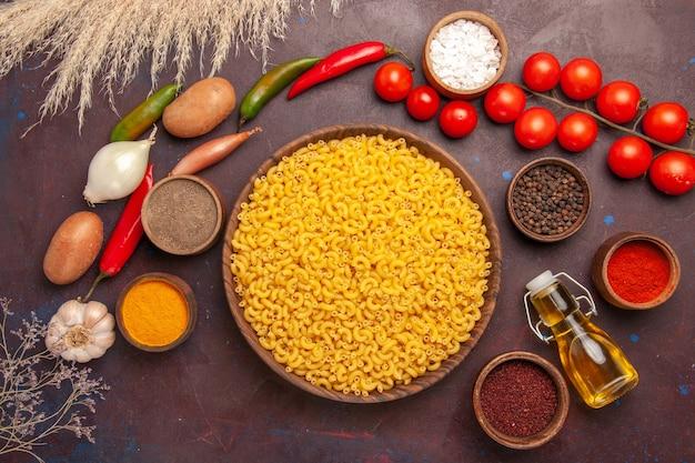 Вид сверху свежие овощи с разными приправами и макаронами на темном столе