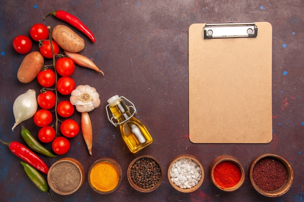 Top view fresh vegetables with different seasonings on dark-purple desk