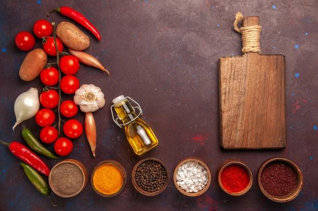 Top view fresh vegetables with different seasonings on dark-purple space