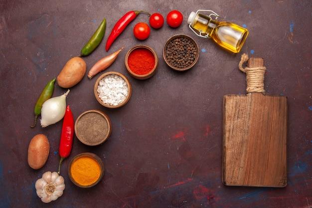 Vista dall'alto di verdure fresche con diversi condimenti nello spazio buio