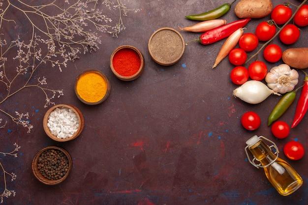 暗い机の上にさまざまな調味料の新鮮な野菜の上面図