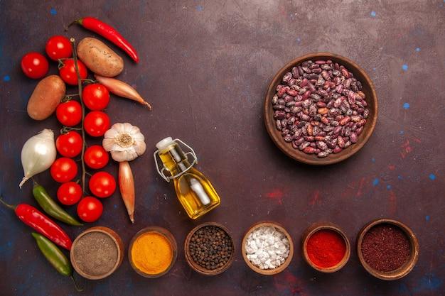 濃い紫色の机の上にさまざまな調味料の新鮮な野菜を上から見る
