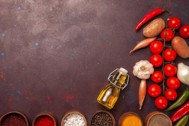 Вид сверху свежие овощи с разными приправами на темно-фиолетовом пространстве