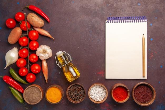 濃い紫色の空間に調味料の異なる新鮮な野菜の上面図