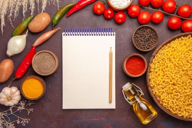 Vista dall'alto di verdure fresche con diversi condimenti e pasta su una scrivania scura