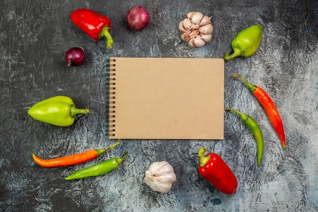 Vista dall'alto verdure fresche con aglio e blocco note sul tavolo grigio chiaro
