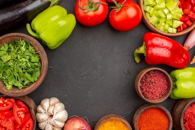 Вид сверху свежие овощи с зеленью и разными приправами на сером фоне еда салат здоровая пища овощ