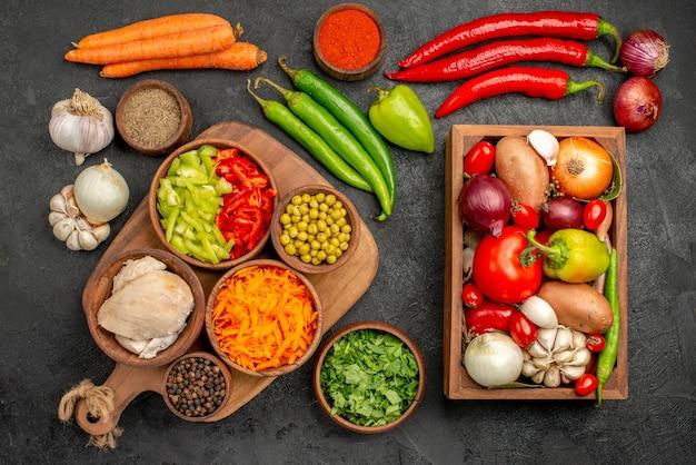 Вид сверху свежие овощи с зеленью и чесноком на темном столе