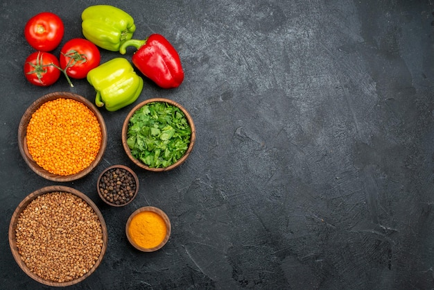 Вид сверху свежие овощи с зеленью и сырой гречкой на сером пространстве