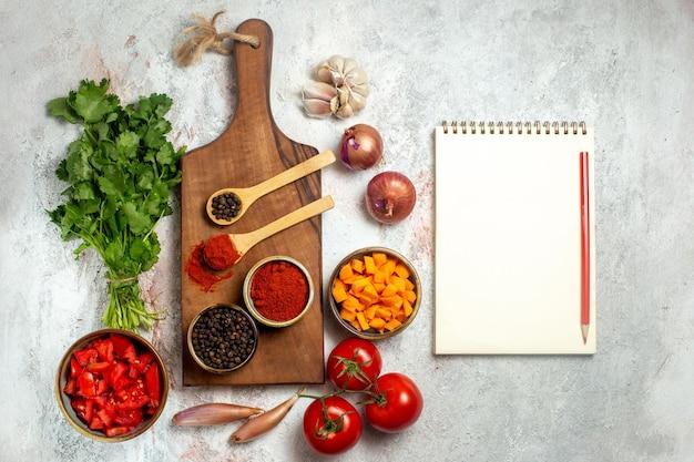 Вид сверху свежие овощи с зеленью и приправами на белом пространстве