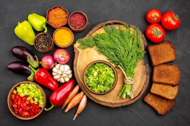 Vista dall'alto verdure fresche con verdure e pagnotte di pane scuro su un pasto salutare per insalata di pane da scrivania scuro