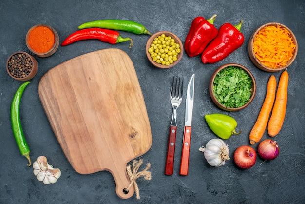 Vista dall'alto di verdure fresche con verdure su verdure insalata matura piano scuro