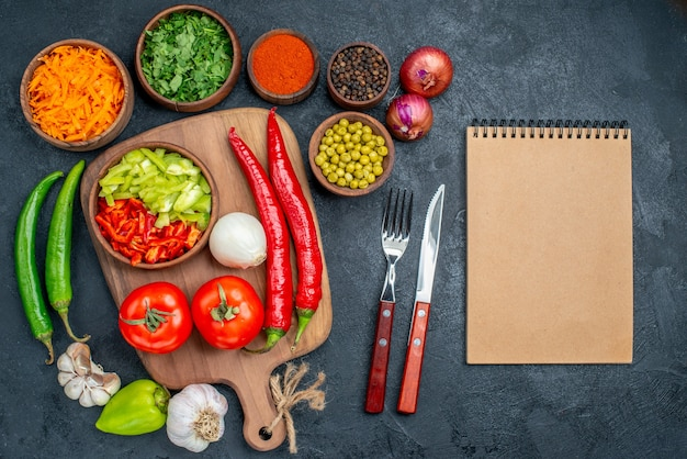 Vista dall'alto di verdure fresche con verdure su tavola scura insalata di verdure colore maturo