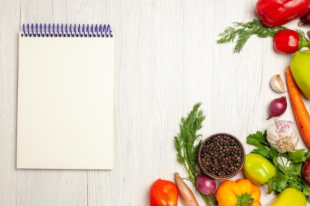 Vista dall'alto di verdure fresche con verdure su insalata verde matura bianca chiara salute