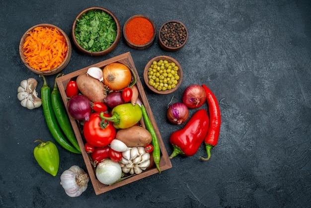 暗いテーブルの色の熟したサラダ野菜の緑と新鮮な野菜の上面図