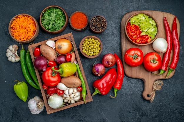 Вид сверху свежие овощи с зеленью на темном столе овощного цвета спелый салат