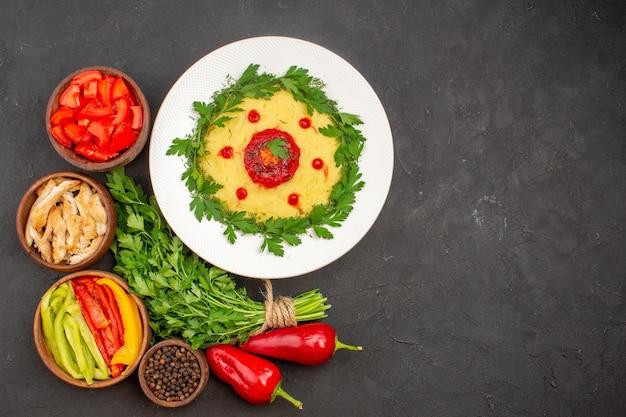Vista dall'alto di verdure fresche con verdure e piatto di patate su nero