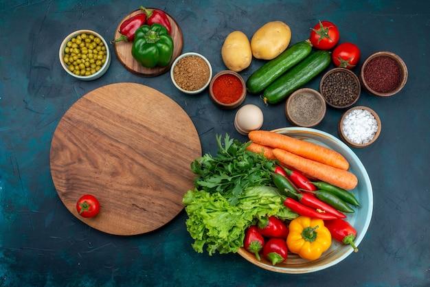 Vista dall'alto di verdure fresche con verdure e condimenti sulla scrivania blu spuntino pranzo insalata di verdure cibo