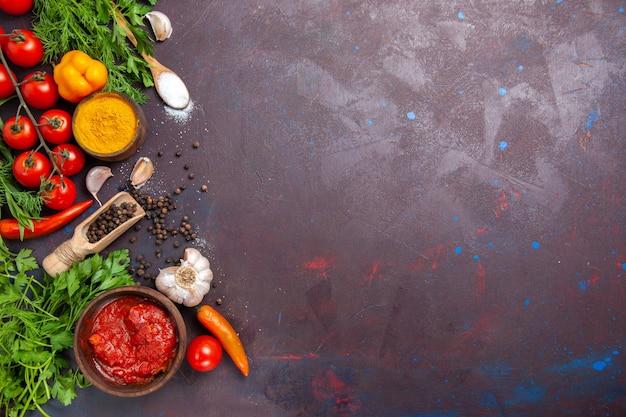 Vista dall'alto di verdure fresche con verdure e condimenti in uno spazio buio