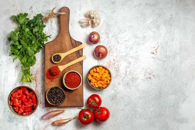 Vista dall'alto verdure fresche con verdure e condimenti su spazio bianco