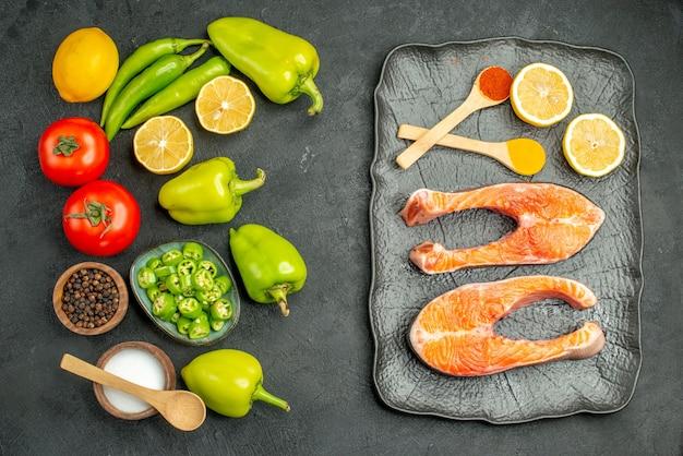 Vista dall'alto verdure fresche con fette di carne su sfondo grigio scuro