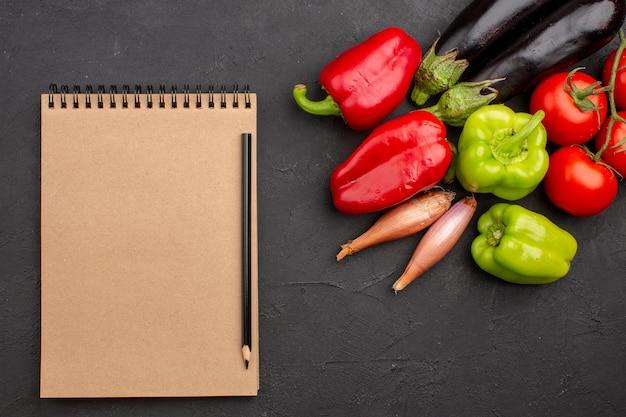 灰色の背景にメモ帳と新鮮な野菜の上面図サラダ野菜の食事の健康