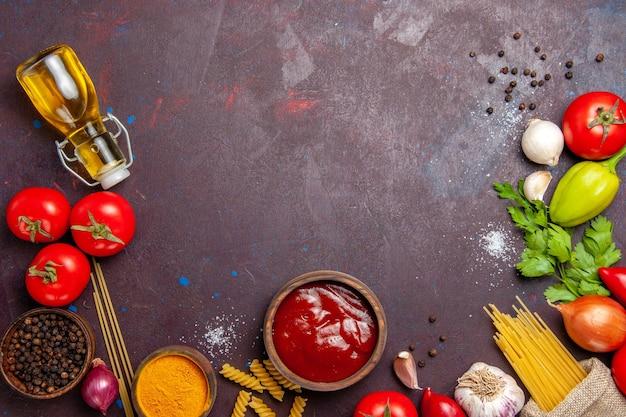Vista dall'alto di verdure fresche con olio e pasta cruda su nero