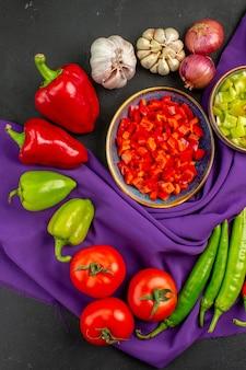 Vista dall'alto di verdure fresche con pepe e aglio sul colore del pasto maturo insalata da tavola scura