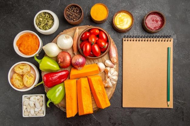 暗い背景のサラダ熟した食事の色にカボチャの調味料と種子と新鮮な野菜の上面図