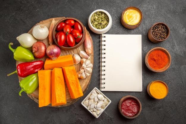 Vista dall'alto verdure fresche con zucca e condimenti su sfondo scuro insalata di colore maturo del pasto