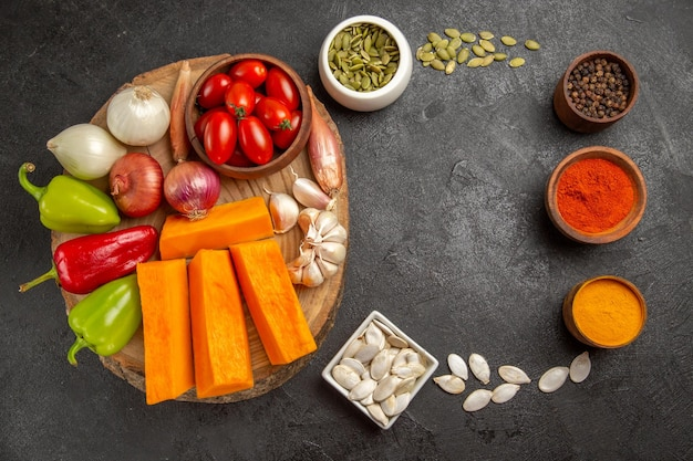 Top view fresh vegetables with pumpkin and seasonings on dark background salad ripe meal color